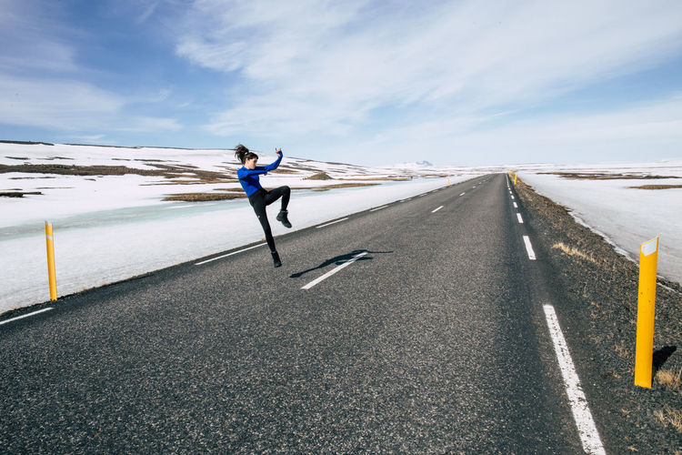 Woman jumping on road against sky during winter