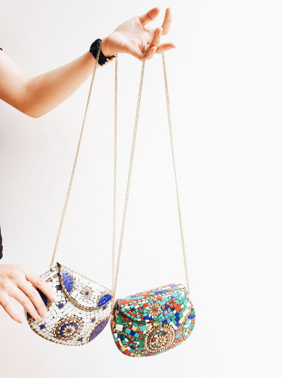 Midsection of woman holding purses against white background