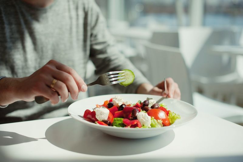 a young man eats a salad in a restaurant overlooking the rivers Food And Drink Food Healthy Eating Wellbeing One Person Freshness Fruit Focus On Foreground Berry Fruit Eating Utensil Vegetable Healthy Lifestyle Plate Real People Hand Table Midsection Salad Human Hand Meal
