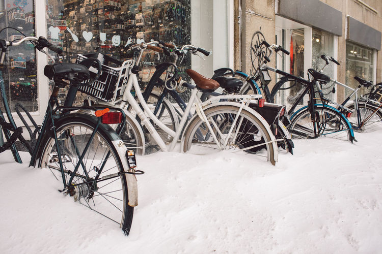 Bicycle leaning on snow covered buildings in city