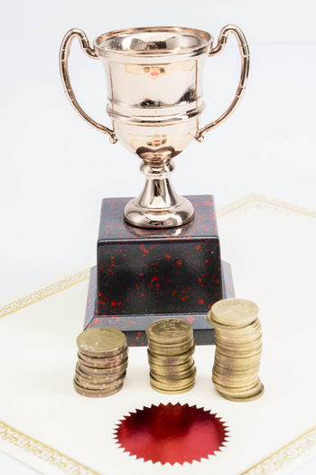 Trophy Cup and coins and blank certificate on white background Still Life Indoors  Studio Shot No People Coin Close-up Finance Stack White Background Table Wealth Success Achievement Investment Metal Savings Large Group Of Objects Currency Cup Business Silver Colored Economy