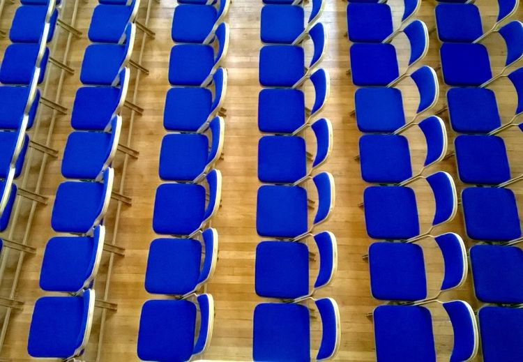 High angle view of empty blue chairs arranged in order at convention center