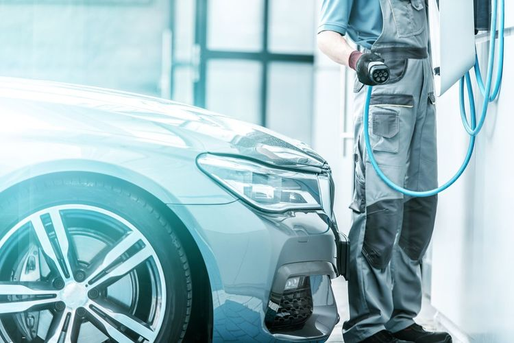 Plug In Hybrid Vehicle and the Charging Station. Worker Preparing To Hookup Modern Vehicle to the Power Outlet. Cars Hybrid Adult Auto Automobile Industry Cable Car Care Charging Station Day Electric Vehicle Electricity  Focus On Foreground Fuel And Power Generation Future Industry Men Mode Of Transportation Motor Vehicle One Person Power Station Renewable Energy Technology Transportation Wheel