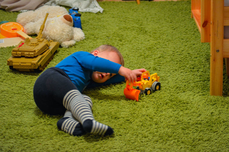 Baby Boy Playing With Toy While Lying On Rug At Home