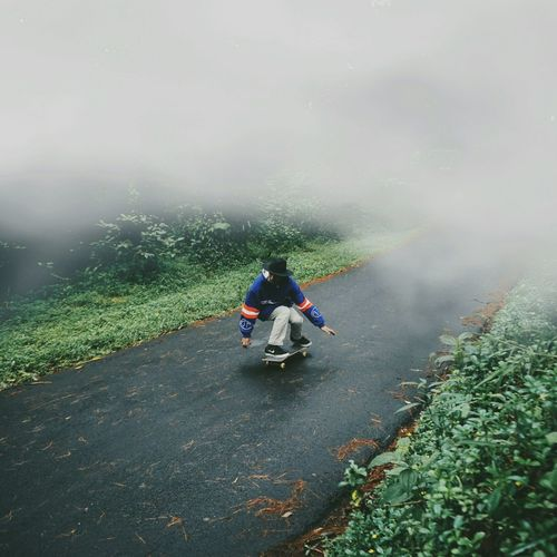 Rear view of man cycling on foggy landscape