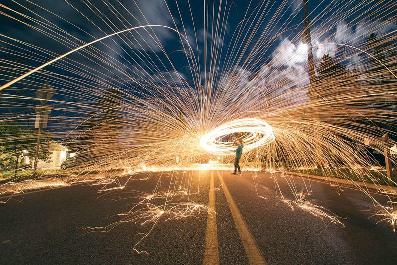 Woman Standing In Illuminated Circle At Night