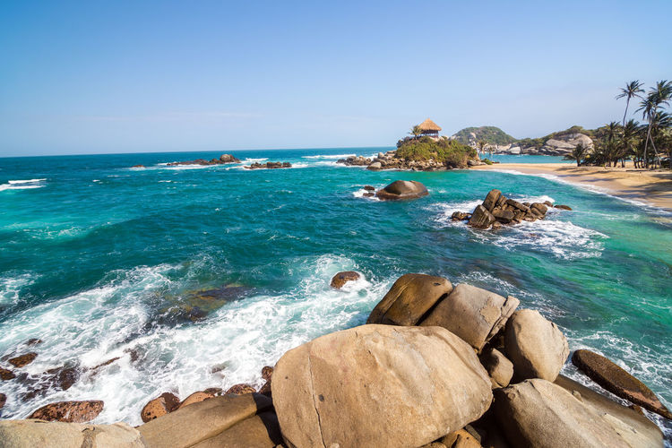 Rock Formations In Sea Against Clear Sky At Tayrona National Park