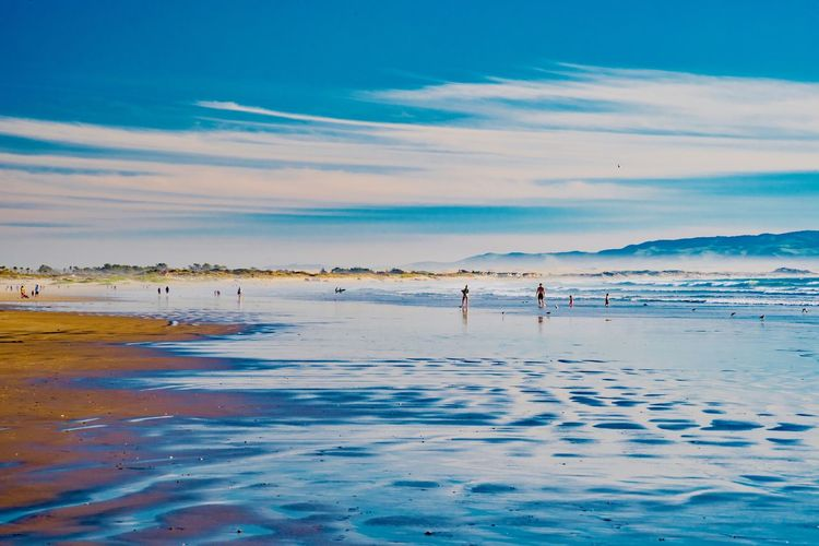Water Land Sea Sky Beach Beauty In Nature Incidental People Nature Scenics - Nature Tranquil Scene Cloud - Sky Tranquility Day Real People Outdoors Idyllic Sport Non-urban Scene Unrecognizable Person