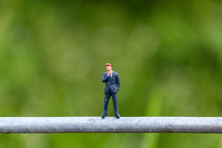 Miniature people : Businessman stand on a wire with green background , Business team concepts Background Business Businessman Closeup Concept Figure Figurine  Financial Green Greeting Human LINE Little Macro Male Man Mini Miniature Model Natural Nature People person Professional Small Standing Success Tiny Toy Worker World Focus On Foreground Day Boundary Outdoors Fence