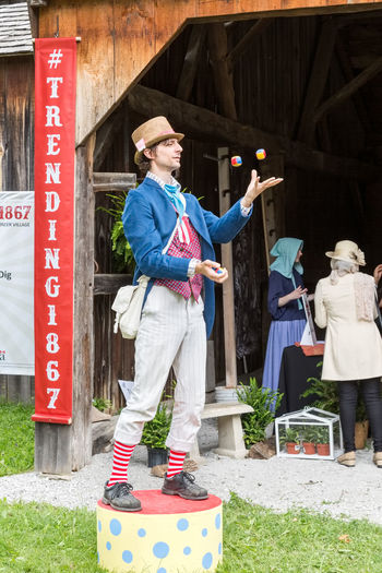 NORTH YORK, CANADA - JULY 01, 2017: A juggler showing his skills at the Black Creek Pioneer Village on the eve of the Canada Day Black Creek Adult Architecture Built Structure Canada Casual Clothing Clothing Communication Day Daylight Full Length Jug Juggling Leisure Activity Lifestyles Males  Men Outdoors People Real People Standing Text Women Young Adult Young Men