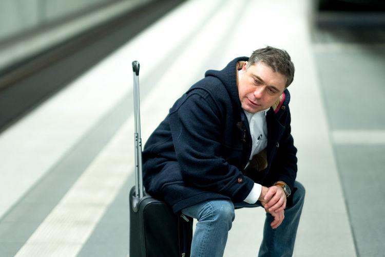 Man sitting on luggage at railroad station platform