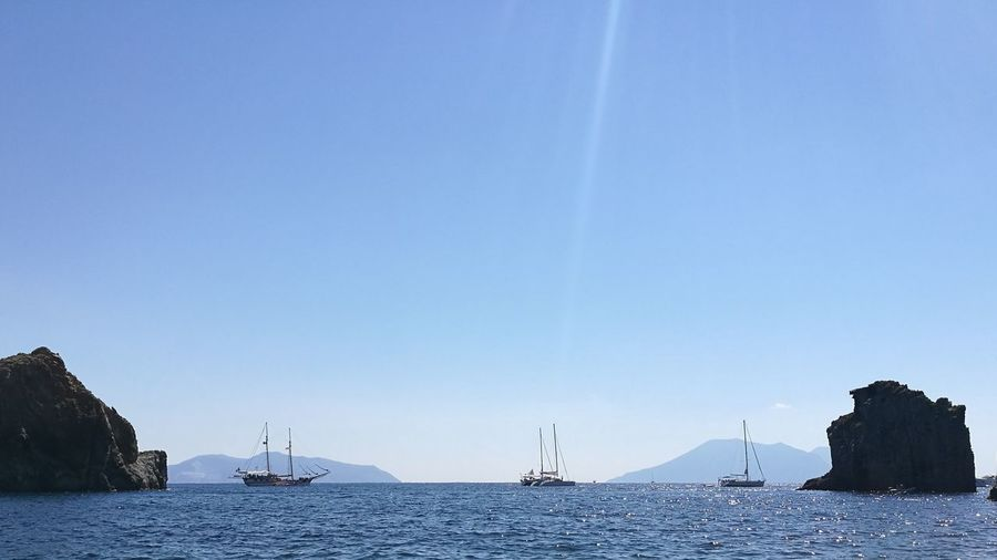 Sailboats in sea against clear sky