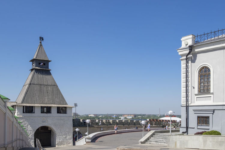 Tower amidst buildings against clear blue sky