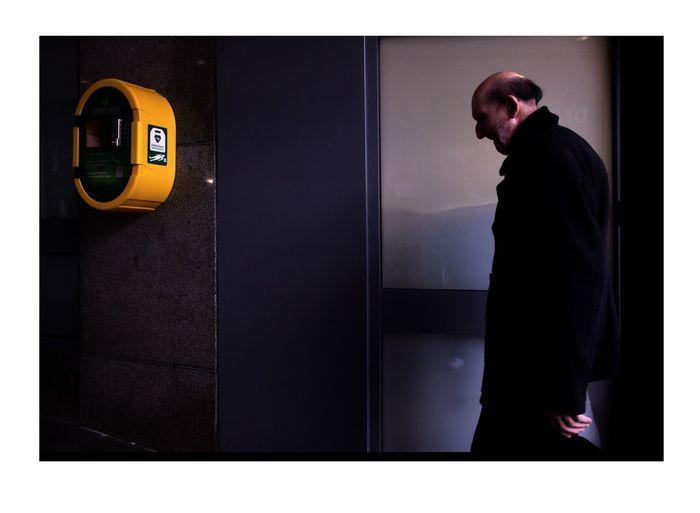 Side view of man standing by door