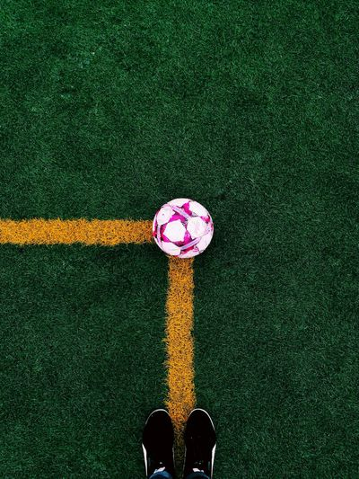 Low Section Of Person Standing On Soccer Field By Ball