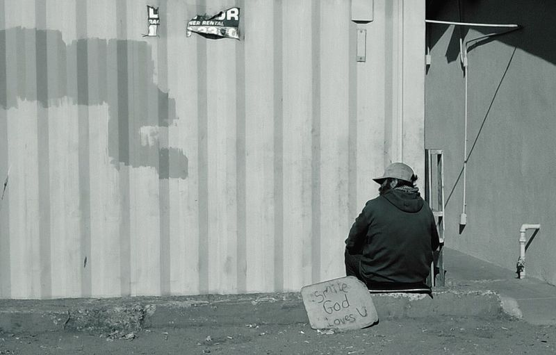 Rear View Of Homeless Man Sitting By Text Against Wall
