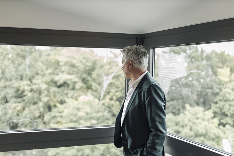 Side view of man standing against window