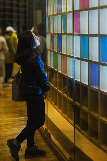 Side view of woman looking at shelves