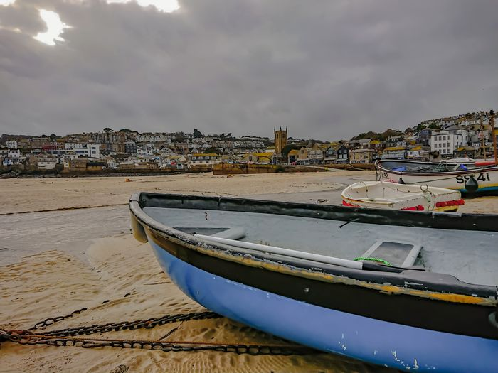 Rowing boat moored on beach Beach Sea Sand City Landscape Water Outdoors Sky Travel Destinations Nature Seascape_lovers Stivesharbour Seascape Photography Seaside Beach Sea Seascape Beachphotography Day Clouds And Sky Scenics Beauty In Nature Building Exterior Rural Scene Horizon Over Water Houses
