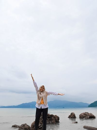 Portrait of woman with arms outstretched standing against sea
