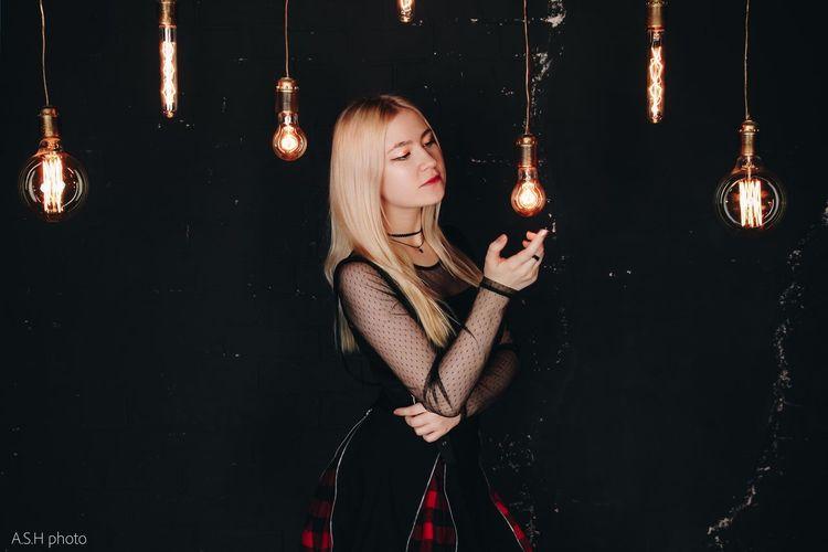 Reflection of woman on illuminated light bulb