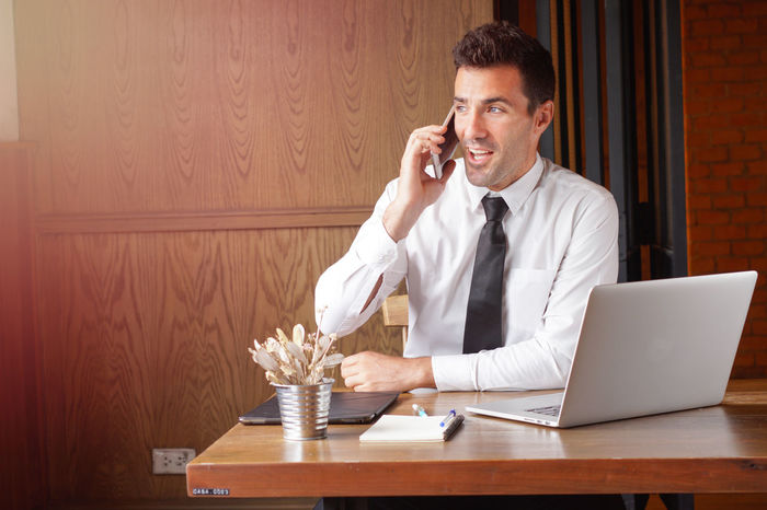Happy Business man talking on the phone. At Work Calling Entrepreneur Happy Negotiating Working Workplace Business Finance And Industry Businessman Ceo Chatting Communication Customer  Delight  Enjoying Life Executive  Laptop Notebook One The Phone Persuations Smile Somebody Talking