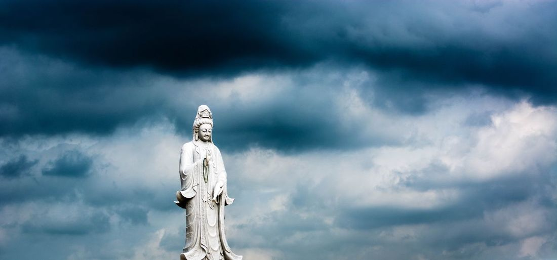 Low angle view buddha statue against storm clouds