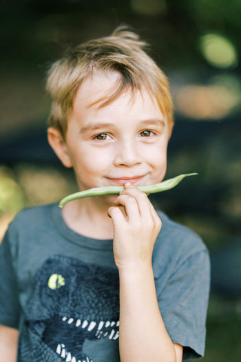Portrait of cute boy holding outdoors
