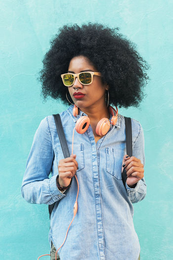 Portrait of beautiful afro american woman in the street. Adult African Afro American Beautiful Casual City Life Copy Space Hair Headphones Lifestyle Woman Adult Attractive Attractive Black Denim Ethnic Hair Outdoors People Portrait Street Sunglasses Urban
