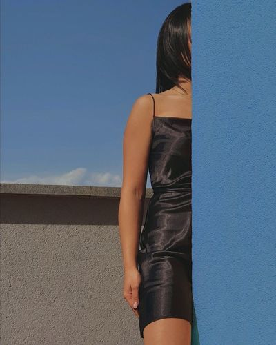 Midsection of woman standing against blue sky