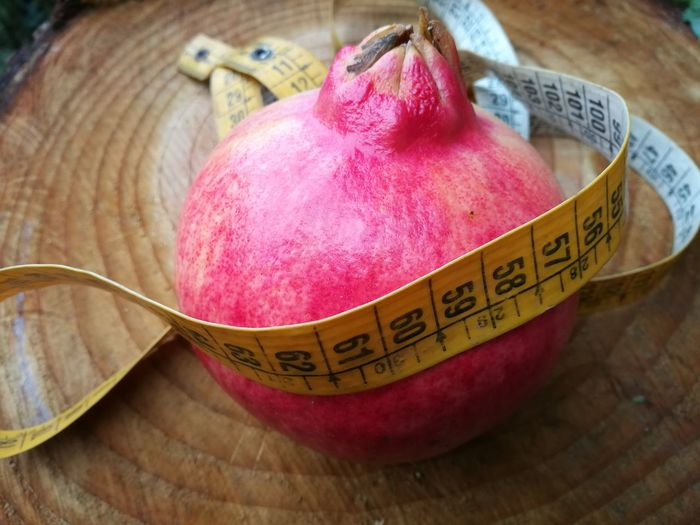 High angle view of pomegranate with tape measure on table