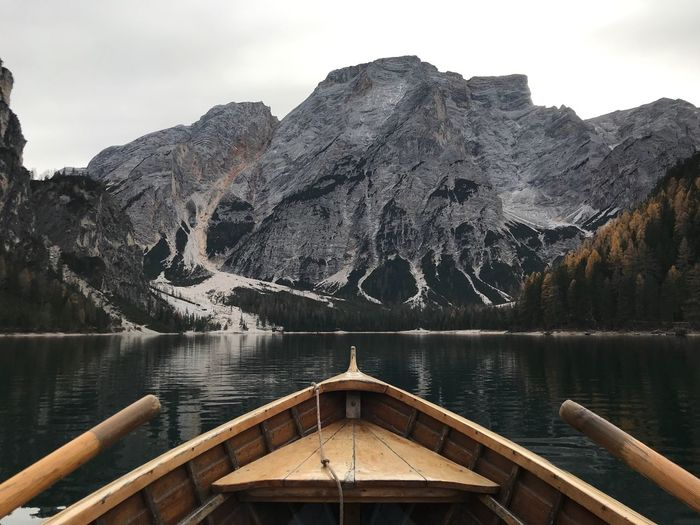 Boat In River Against Majestic Mountains