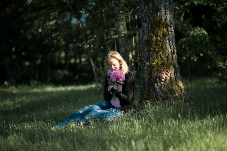Young woman smelling flowers while sitting on grassy field in forest