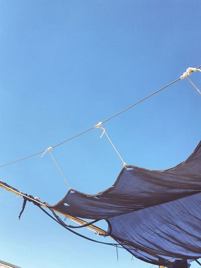 Low angle view of canvas against clear blue sky