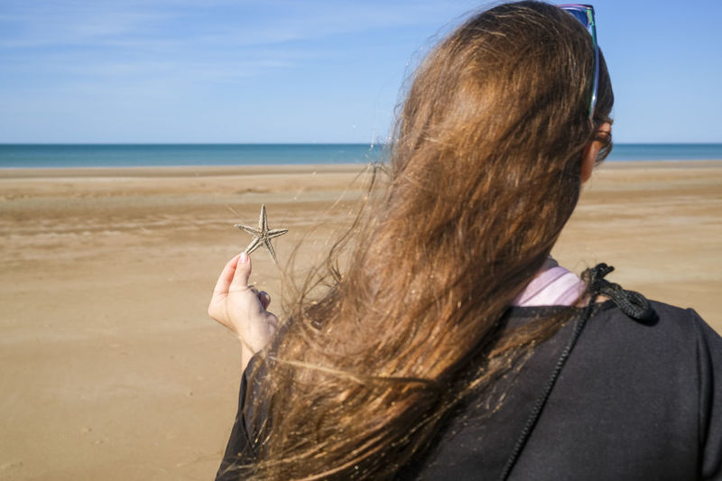 Rear view of woman at beach against sky