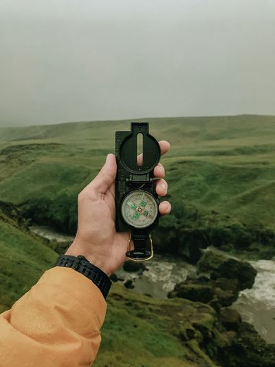 Cropped hand holding navigational compass against landscape