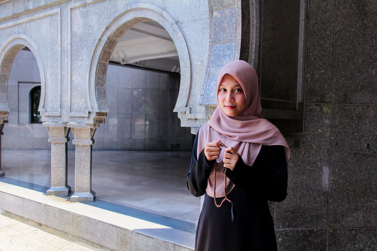 Portrait of woman in hijab holding counting rosary beads while praying at mosque