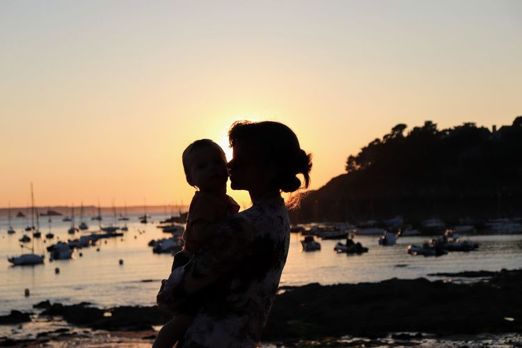 Woman kissing son at beach against sky during sunset