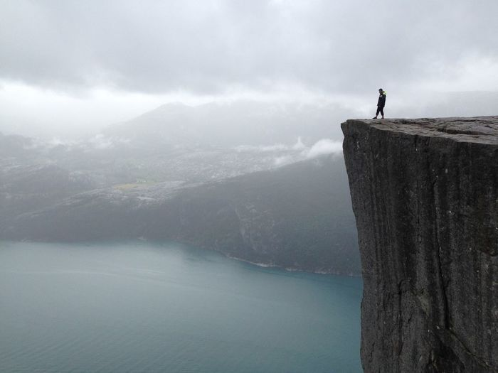 Distant view of man standing at preikestolen against cloudy sky