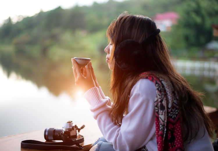 Midsection of woman holding drink sitting outdoors