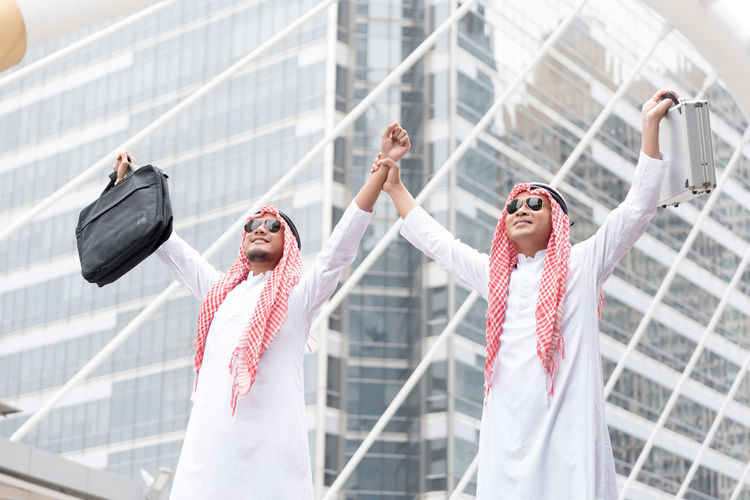 Businessmen in traditional clothing standing against skyscraper