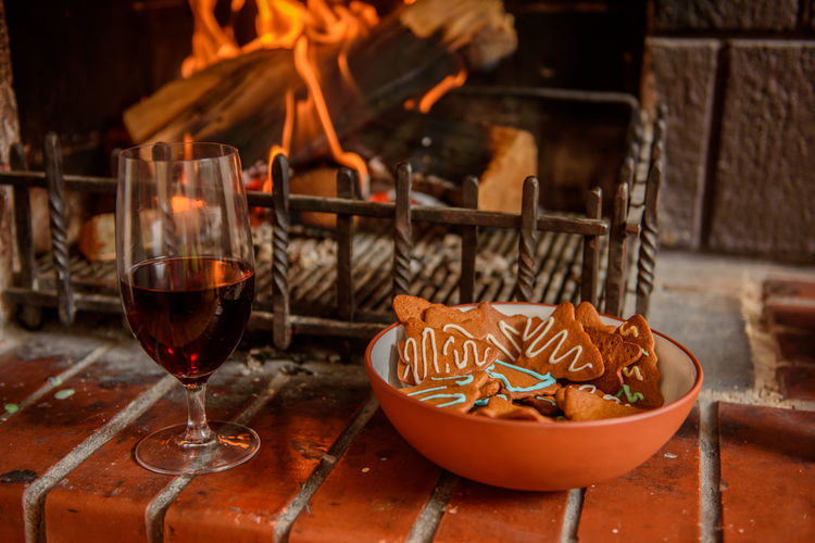 Gingerbreads, mulled wine near open fire place. Food And Drink Food Glass Freshness Wine Alcohol Red Wine Flame Fire - Natural Phenomenon Heat - Temperature Wineglass Burning Fire Drink Mulled Wine Christmas Christmas Illustration Focus On Foreground Wood - Material Heating Fire Place Family Time
