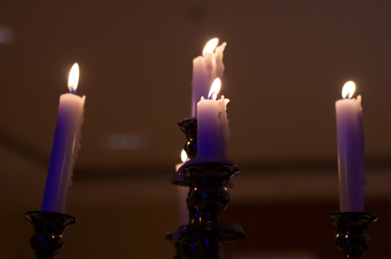 Close-up of lit candles against wall