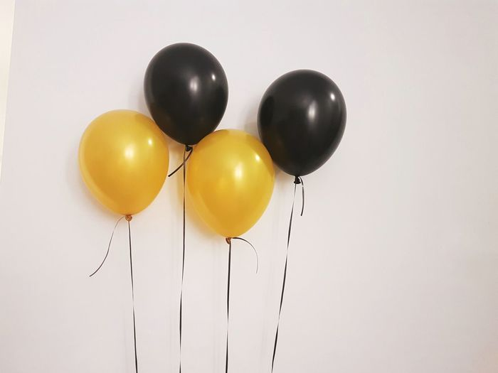 Low angle view of balloons against white background
