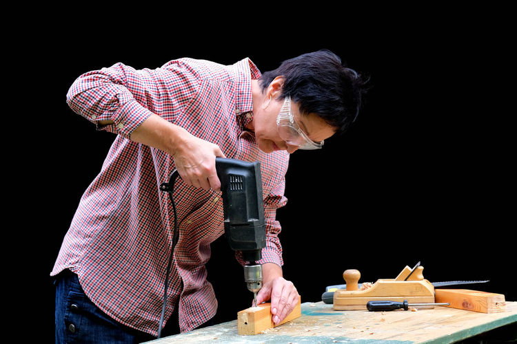 Man working on table against black background