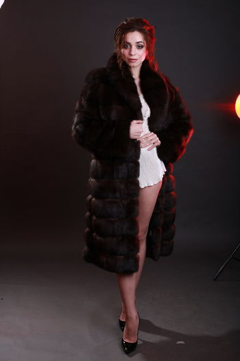 Beautiful Woman Indoors  Clothing Standing Studio Shot Studio Photography Editorial Photography Elégance Warm Clothing Fur Coat Fur Glamour Fashion Model Gray Background One Person Looking At Camera Full Length Portrait Fashion Women Hairstyle Smiling Holding Confidence  Black Background
