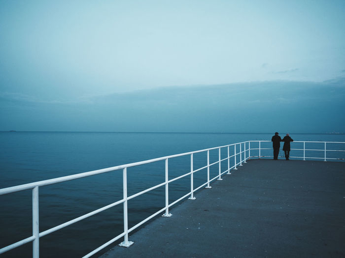 Rear view of people standing by railing against sea