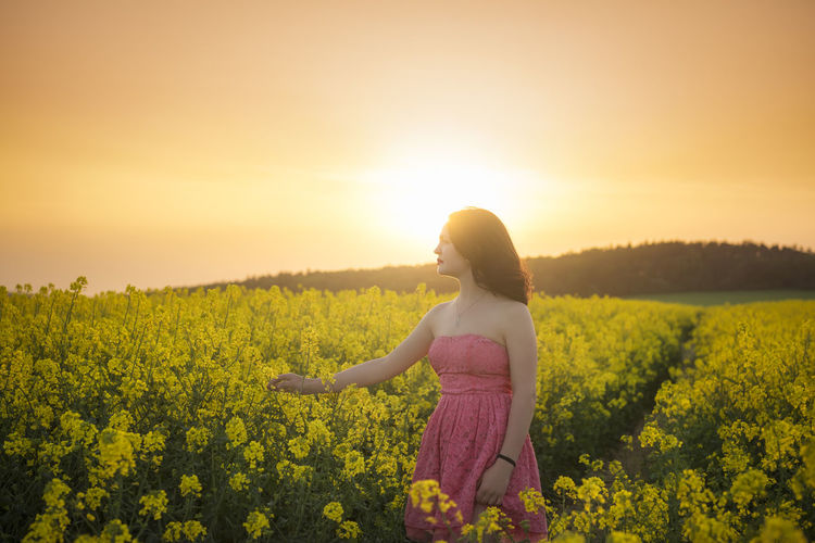 Woman Standing Amidst Yellow Flowering Plants On Field Against Sky During Sunset