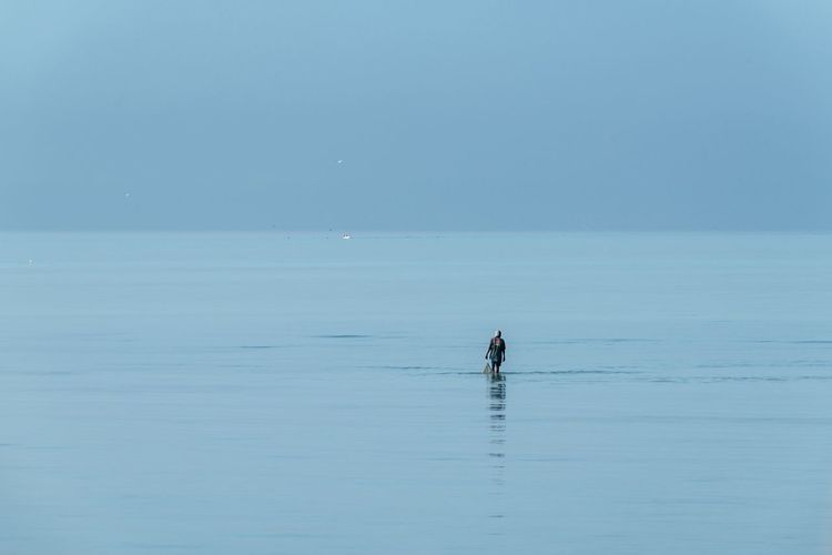 Distant view of man in sea against sky