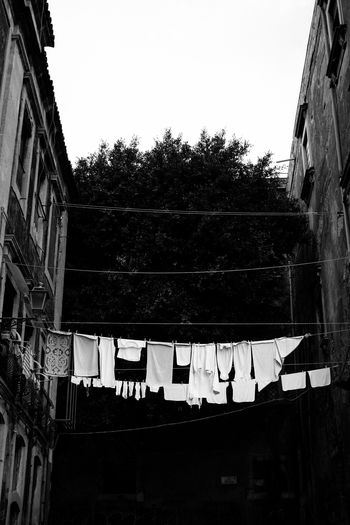 Low angle view of clothes hanging on building against clear sky
